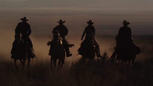 slow motion panning shot of four cowboys riding horses - cowboy stock-videos und b-roll-filmmaterial