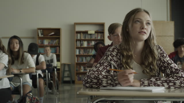 vidéos et rushes de slow motion panning shot of girl taking notes in school classroom / provo, utah, united states - salle de classe
