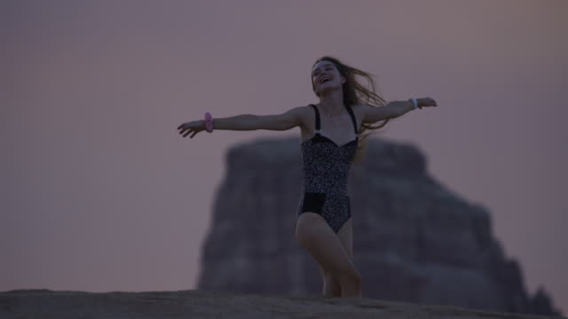 slow motion panning shot of girl with cell phone recording spinning friend at dusk / glen canyon national park, utah, united states - dreiviertelansicht stock-videos und b-roll-filmmaterial