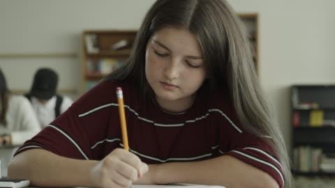 vídeos y material grabado en eventos de stock de slow motion panning shot of girl writing in notebook in school classroom / provo, utah, united states - escritorio