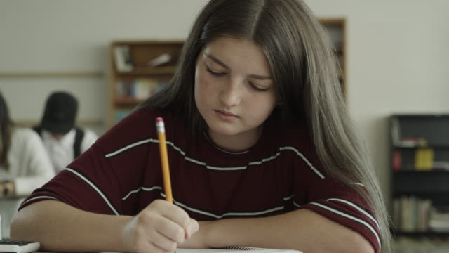 slow motion panning shot of girl writing in notebook in school classroom / provo, utah, united states - junior high stock videos & royalty-free footage