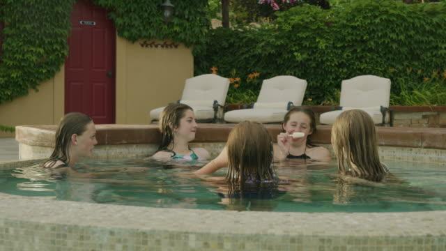 slow motion panning shot of girls relaxing in backyard swimming pool / cedar hills, utah, united states - utebassäng bildbanksvideor och videomaterial från bakom kulisserna