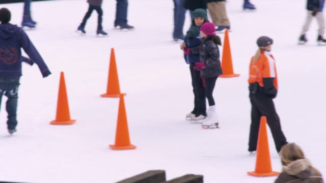 slow motion panning shot of ice skaters on the central park ice rink. - ice skating stock videos & royalty-free footage