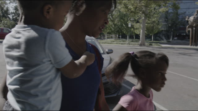 slow motion panning shot of mother carrying son walking with daughter on city sidewalk / provo, utah, united states - provo stock-videos und b-roll-filmmaterial