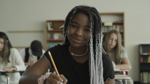 slow motion panning shot of portrait of smiling girl in school classroom / provo, utah, united states - zöpfchenfrisur stock-videos und b-roll-filmmaterial