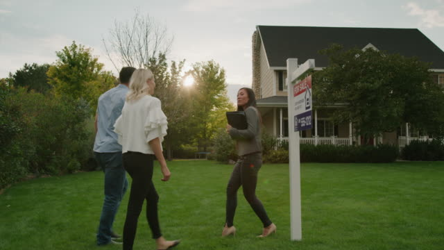 slow motion panning shot of realtor talking with couple on lawn of house for sale / pleasant grove, utah, united states - 住宅購入点の映像素材/bロール