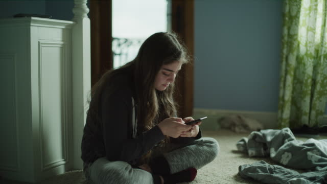 slow motion panning shot of sad girl sitting on floor reading cell phone / cedar hills, utah, united states - usare il telefono video stock e b–roll