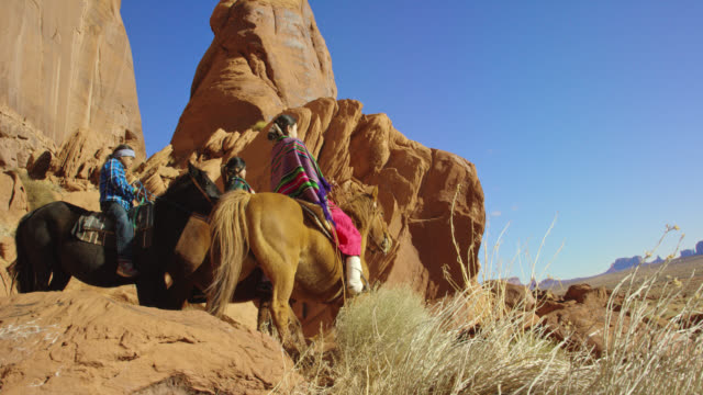 slow motion panning shot of several young native american (navajo) children wearing traditional navajo clothing and riding their horses through the landscape of the monument valley desert in arizona/utah next to a large rock formation on a clear, bright d - group of animals stock videos & royalty-free footage