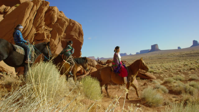 slow motion panning shot of several young native american (navajo) children wearing traditional navajo clothing and riding their horses through the landscape of the monument valley desert in arizona/utah next to a large rock formation on a clear, bright d - small group of animals stock videos & royalty-free footage