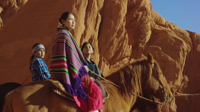 slow motion panning shot of several young native american (navajo) children wearing traditional navajo clothing and sitting on their horses and looking out at the landscape of the monument valley desert in arizona/utah next to a large rock formation on a - horse family stock videos & royalty-free footage