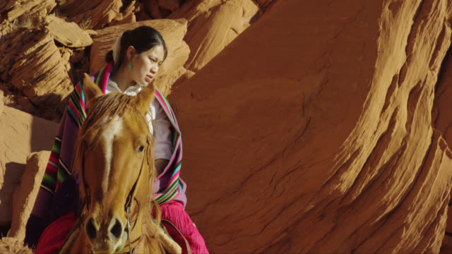 slow motion panning shot of several young native american (navajo) children sitting on their horses in the monument valley desert in arizona/utah next to a large rock formation on a clear, bright day - navajo stock videos & royalty-free footage