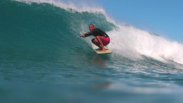 slow motion panning shot of skilled man crouching while surfing on wave - oahu, hawaii - squatting position stock videos & royalty-free footage