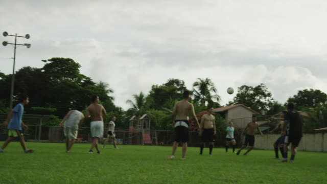 Slow motion panning shot of soccer teams playing on field / Esterillos, Puntarenas, Costa Rica