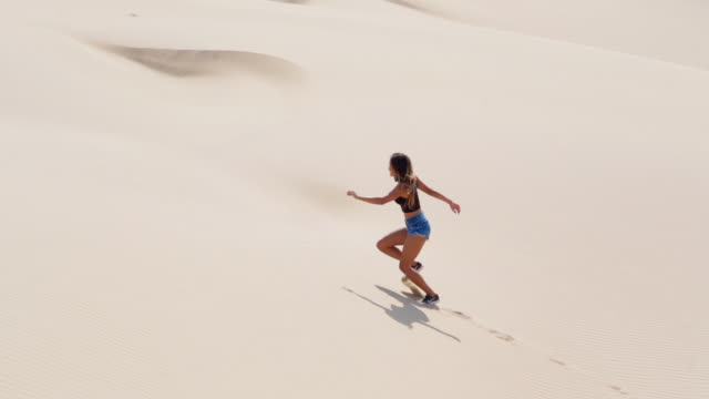 slow motion panning shot of tourist climbing up on sand dune in desert, full length side view of young woman on sunny day - huacachina, peru - full length bildbanksvideor och videomaterial från bakom kulisserna