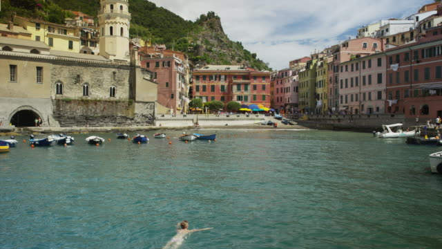 Slow motion panning shot of woman swimming in village harbor / Vernazza, Cinque Terre, Italy