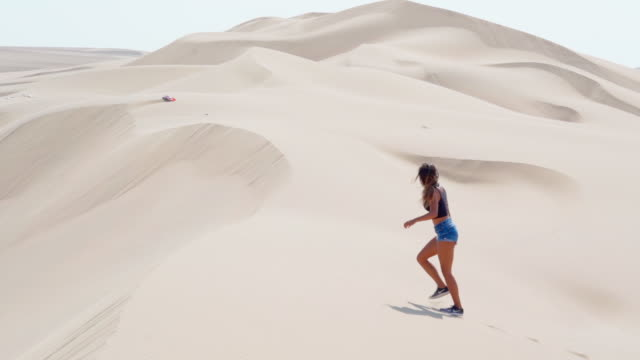 slow motion panning shot of young woman walking on sand dune in desert, full length side view of tourist on sunny day - huacachina, peru - full length bildbanksvideor och videomaterial från bakom kulisserna
