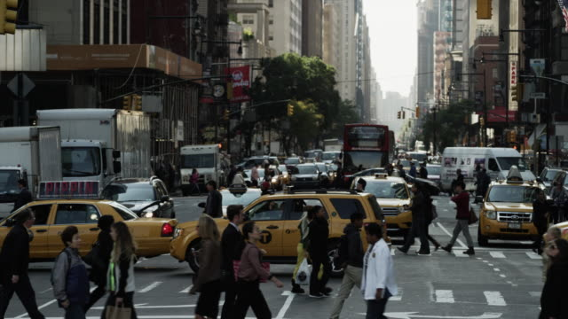 Slow motion panning wide shot of bustling city street / New York City, New York, United States