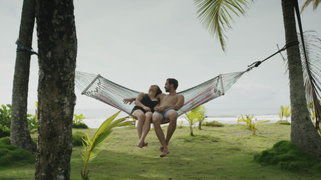 slow motion panning wide shot of couple sitting in hammock / esterillos, puntarenas, costa rica - hammock stock videos & royalty-free footage