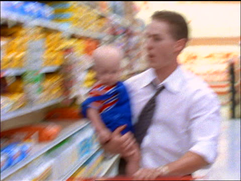 slow motion pans businessman pushing shopping cart thru aisle of grocery store while holding baby boy - genderblend stock videos & royalty-free footage