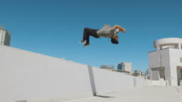 Slow motion parkour athlete doing extreme backflip off wall in urban city outside isolated in sky