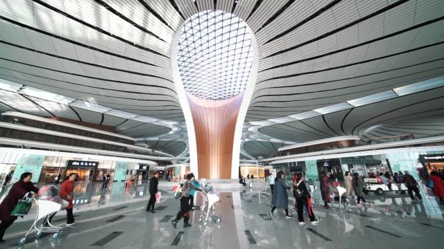 stockvideo's en b-roll-footage met slow-motion passagiers op een voetgangers voetpad in beijing daxing airport terminal in china - peking