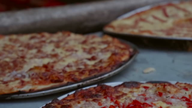 slow motion: passing across several cooked pizzas still on their baking trays in el limon, dominican republic - hispaniola stock videos & royalty-free footage