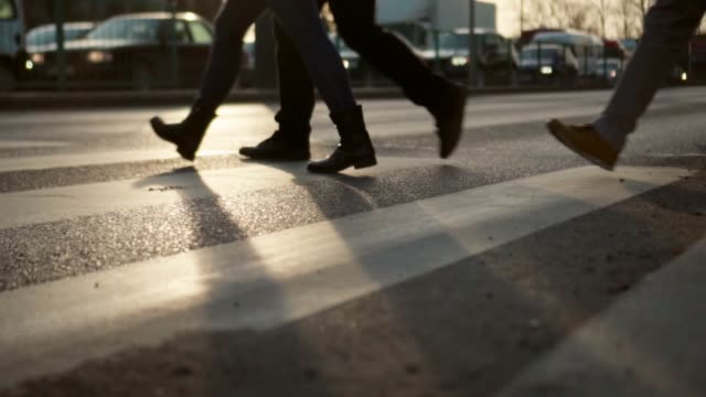slow motion: pedestrian crosswalk at sunset - zebra crossing stock videos & royalty-free footage