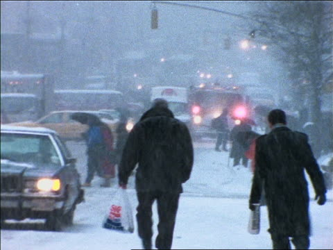 slow motion pedestrians + traffic on city street in snowstorm / NYC