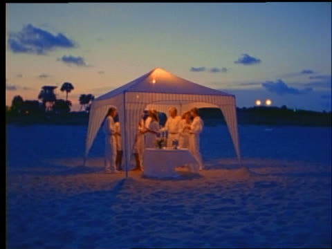 slow motion pan of people at party under canopy on beach / dusk / grainy - gazebo stock videos and b-roll footage