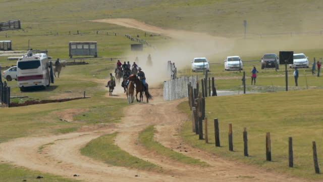 slow motion: people horseback riding on dirt road amidst land during race - ulaanbaatar, mongolia - independent mongolia stock videos & royalty-free footage