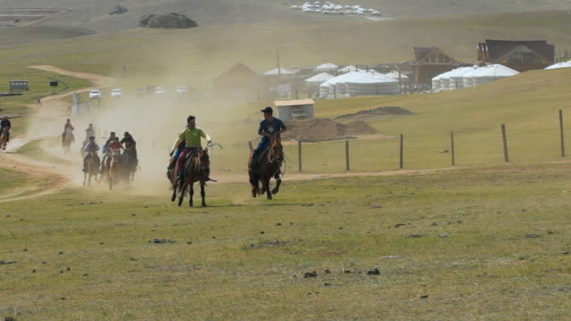 slow motion: people horseback riding on field against mountain during sports race - ulaanbaatar, mongolia - ulan bator stock videos & royalty-free footage