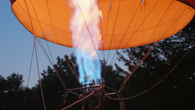 slow motion: people inside hot air balloon & open flame heating air inside - balloon stock videos & royalty-free footage