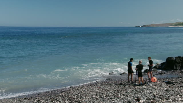 vidéos et rushes de slow motion people stand along shore in reunion island - dom tom