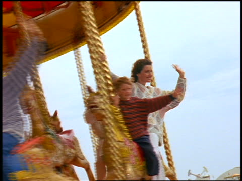 slow motion people waving + riding on carousel at victorian palace pier amusement park / brighton - 回転遊具点の映像素材/bロール