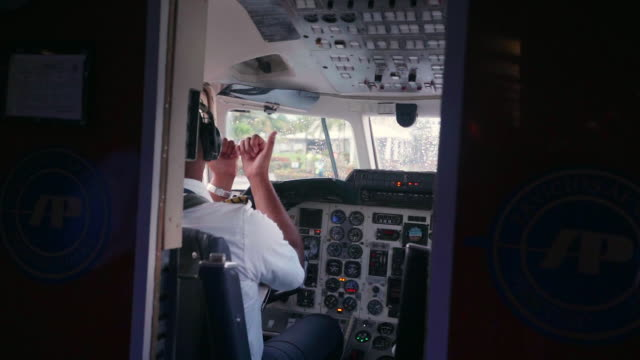 slow motion: pilot in cockpit gesturing to someone outside - captain stock videos and b-roll footage