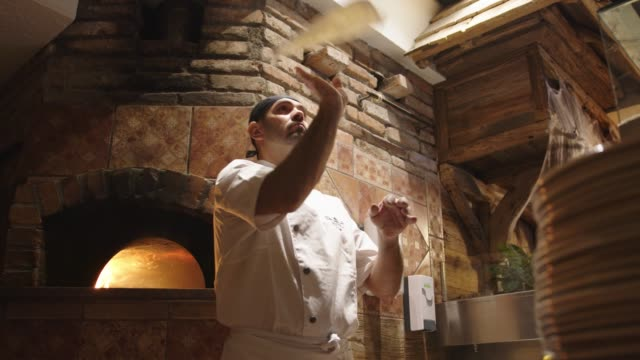 slow motion - pizza master tossing the pizza dough in the air - italian culture stock videos & royalty-free footage