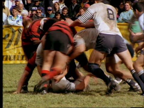 slow motion players piling up in tackle / rugby match