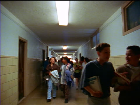 slow motion point of view students walking toward + away from camera in hallway of junior high school - secondary school child stock videos & royalty-free footage