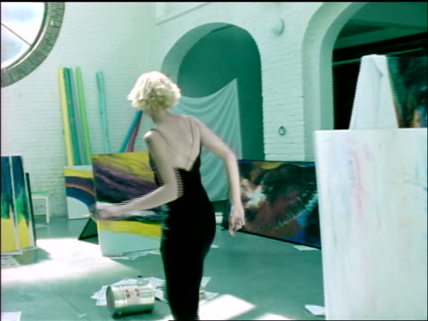 slow motion point of view young blonde woman dancing + smiling for camera around paintings in large studio