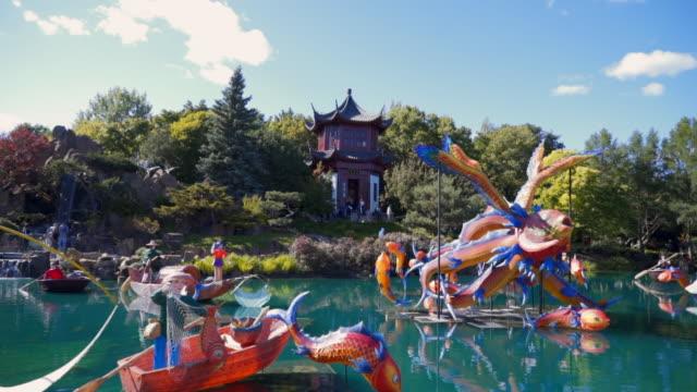 slow motion: pond in japanese garden with fantastical sculptures - skulptur kunstwerk stock-videos und b-roll-filmmaterial