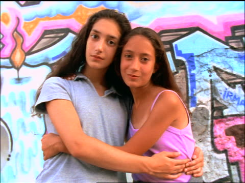 vidéos et rushes de slow motion portrait 2 girls hugging + laughing in front of graffiti-covered wall - fratrie