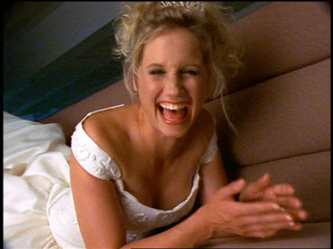 slow motion portrait blonde bride lying on couch of bowling alley snack bar + laughing at camera - augen zuhalten stock-videos und b-roll-filmmaterial