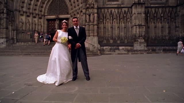vidéos et rushes de slow motion portrait bride + groom standing together in front of cathedral / barcelona, spain - le marié