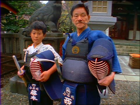 slow motion portrait dolly shot in to japanese man + small boy standing with kendo gear / japan - 小学校低学年点の映像素材/bロール