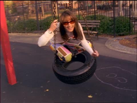 vídeos de stock e filmes b-roll de slow motion portrait hispanic woman with sunglasses sitting on tire swing + laughing on playground / nyc - equipamento de parque infantil