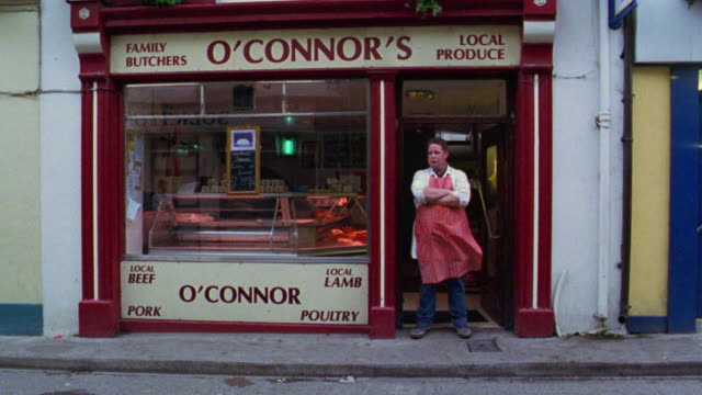 "slow motion PORTRAIT male butcher stands with arms crossed in doorway of ""O'Connor's"" butcher shop / Dublin"
