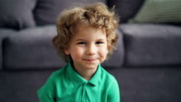 Slow motion portrait of cute little boy looking at camera and smiling at home