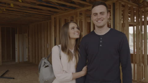 slow motion portrait of smiling couple in interior of home under construction / pleasant grove, utah, united states - husband stock videos & royalty-free footage