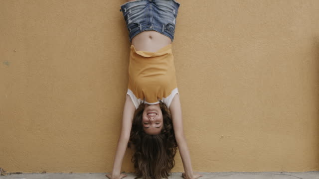 slow motion portrait of smiling girl performing handstand against wall / provo, utah, united states - upside down stock videos & royalty-free footage