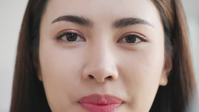 slow motion: portrait of woman with glossy lips applying cream. - skin feature stock videos & royalty-free footage